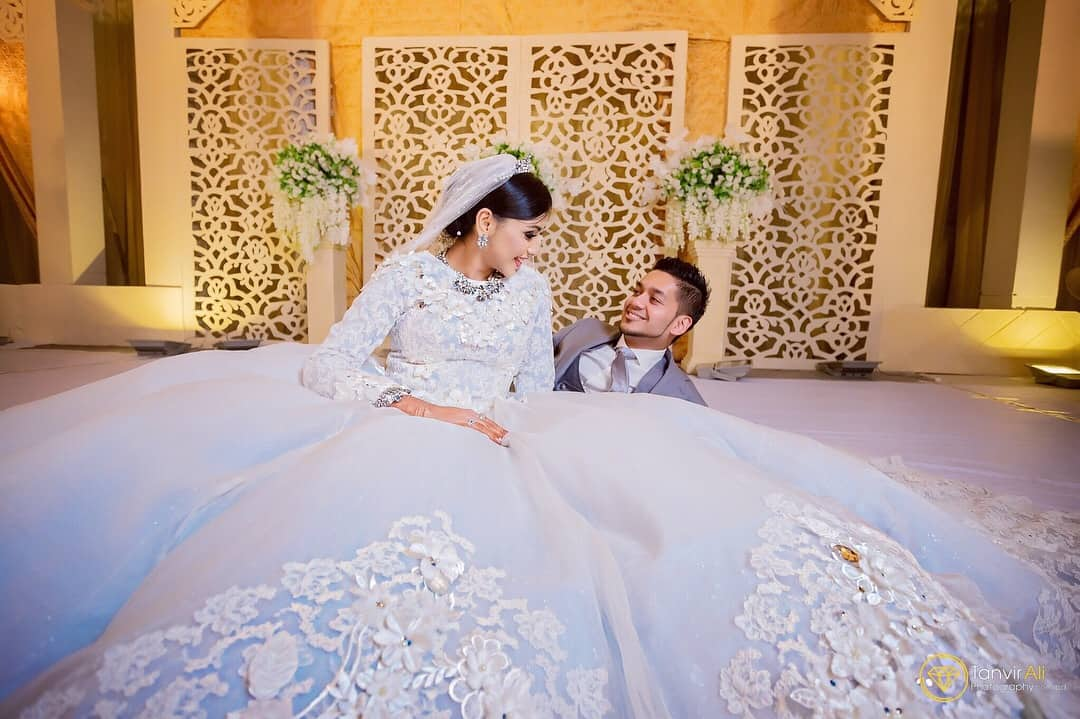groom sits beside bride who is sitting next to him in large custom wedding gown Toronto Custom wedding dresses