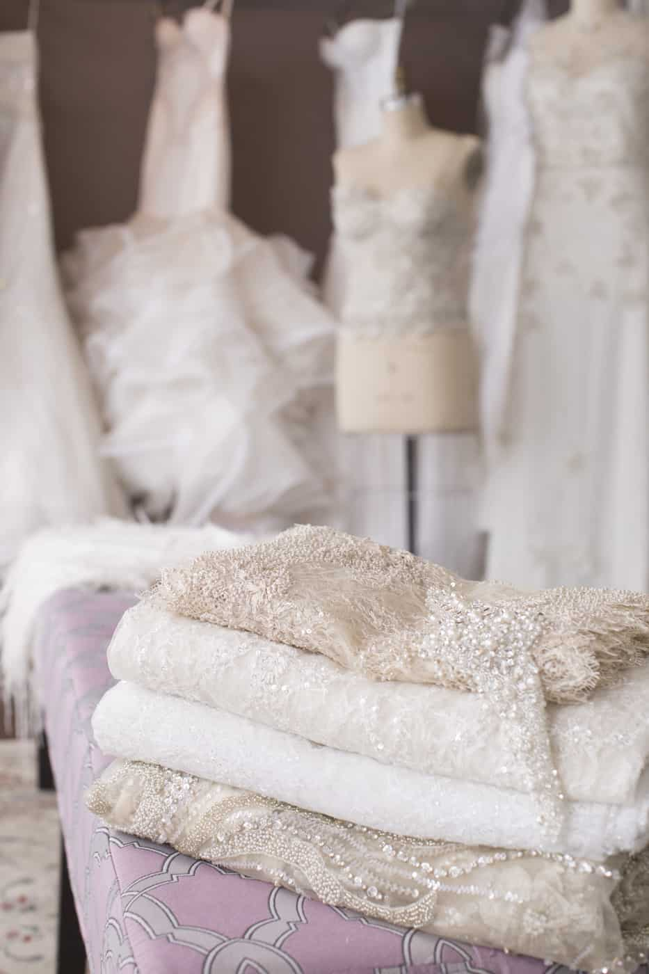 wedding dress textiles piled on a table in front of finished wedding dresses Valencienne Bridal