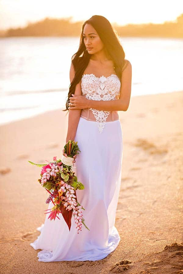 bride walking down a beach at sunset holding floral bouquet custom wedding dress