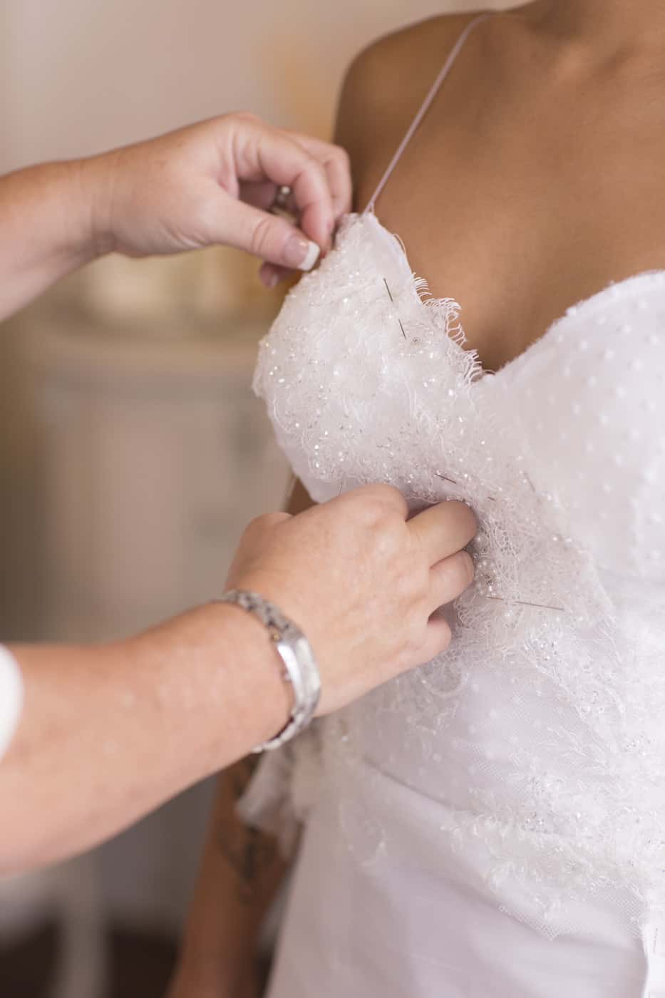 seamstress putting finishing touches on brides dress Valencienne