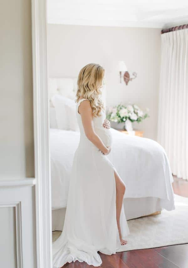 Pregnant bride holding baby bump in her chiffon wedding gown