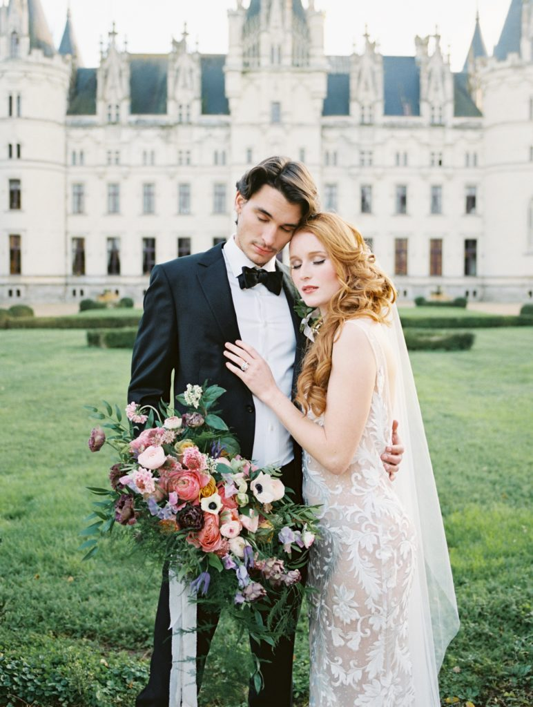 Bride in Valencienne Desiree Wedding Gown embracing with Groom in front of French chateau.