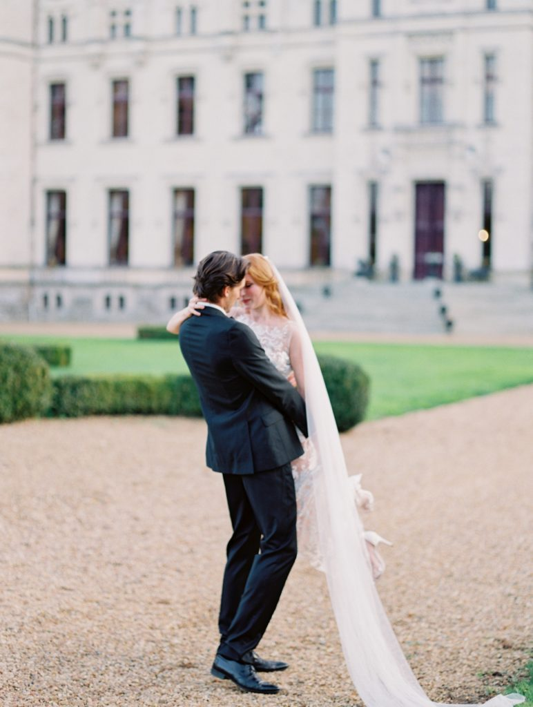 Bride and groom twirling in Valencienne Bridal Desiree Gown in front of French Chateau.